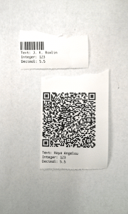Two paper labels. One label has a 1D barcode and some text. The other has a QR code and some text.